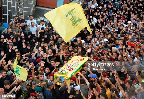 Mourners carry the coffin of a fighter from Lebanon's Shiite Hezbollah movement who was killed in conflict against militant groups in the mountainous...