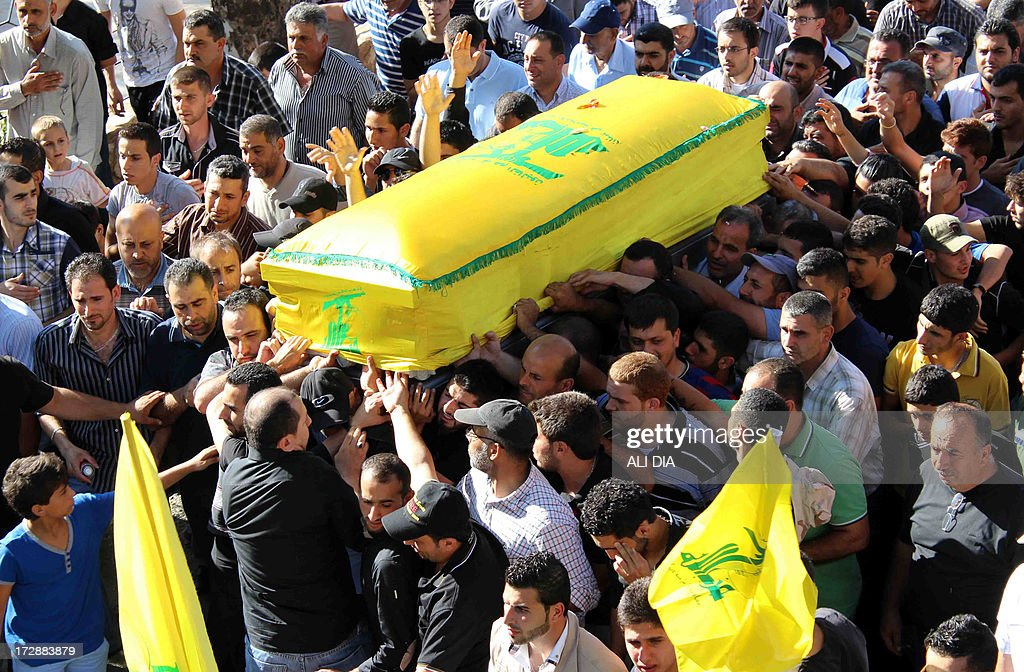 Mourners carry the coffin of a Lebanese Hezbollah fighter, draped in the flag of the Lebanese Shiite Muslim party, who was killed in Syria during his funeral procession on July 5, 2013 in the southern Lebanese village of Khiam. Hezbollah, a long-time ally of President Bashar al-Assad's government, has been increasingly involved in the Syrian conflict now its third year, with militants battling alongside the Syrian army against the mostly Sunni Muslim rebel fighters.