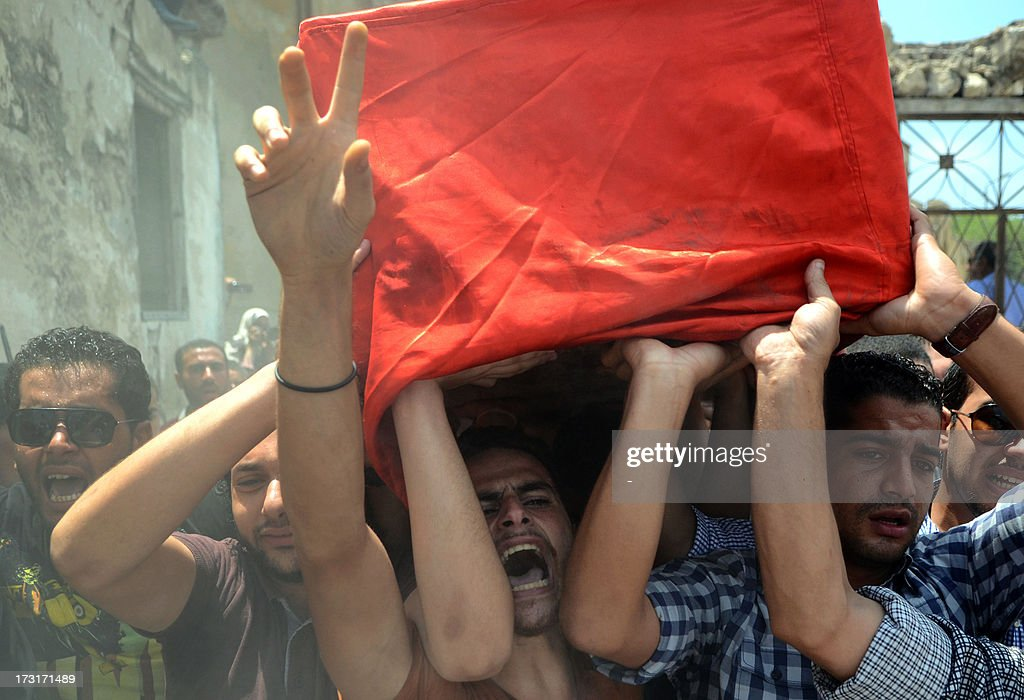 Mourners carry the coffin of a police officer killed in clashes between protestors and security forces during his funral in the northern coastal city of Alexandria on July 9, 2013. Egypt's interim leader vowed fresh elections by early next year as Islamists prepared to rally after dozens of ousted president Mohamed Morsi's loyalists died in clashes at a Cairo military barracks the day before. The Muslim Brotherhood released the names of 42 people killed in the incident, as the interior ministry and military said two policemen and a soldier were also killed.
