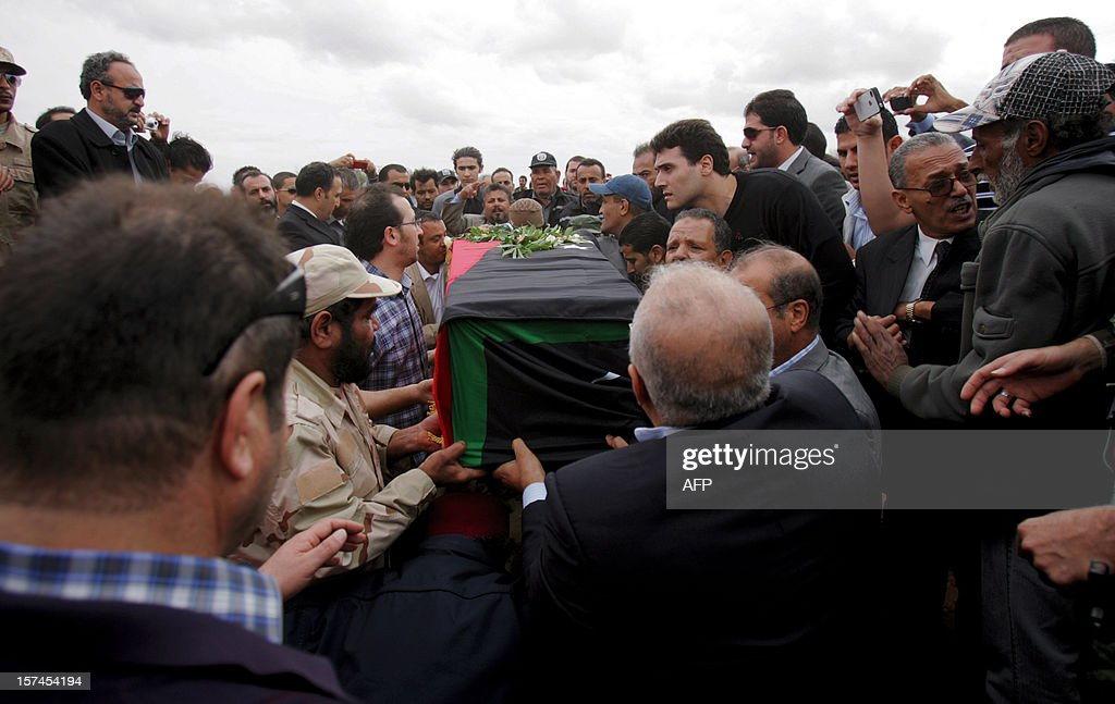 Mourners carry the coffin of leading Libyan dissident Mansour al-Kikhia during his funeral procession in the eastern Libyan port city of Benghazi on December 3, 2012. Kikhia, who disappeared 19 years ago under the Kadhafi regime, was buried, weeks after his body was found in an intelligence services morgue, his brother said.