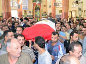 Mourners carry the coffin of Mahmud Taha one of the Egyptian policemen who were killed the day before in alArish on October 17 2014 during his...
