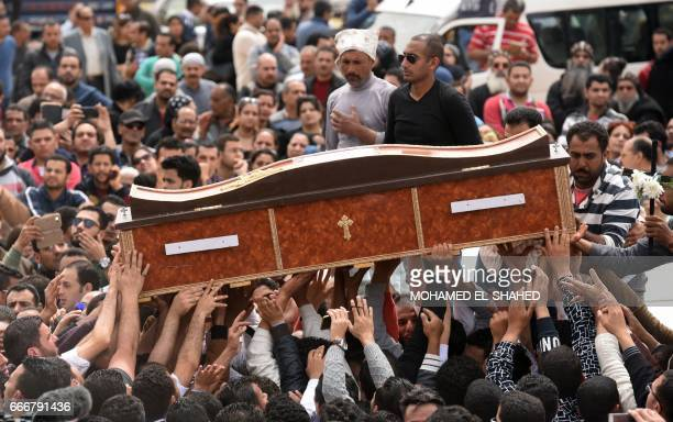 Mourners carry the coffin of one of the victims of the blast at the Coptic Christian Saint Mark's church in Alexandria the previous day during a...