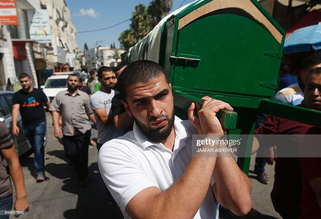 Mourners carry the coffin of Sondos al-Basha, a Palestinian woman who was killed in the Istanbul airport attack blamed on the Islamic State (IS) group on June 28, during her funeral in the West Bank town of Qalqilyah on July 1, 2016. The suicide attackers who launched the deadly Istanbul airport assault were planning to take dozens of passengers hostage, Turkish media reported on July 1, 2016, as CCTV of the bombers' faces emerged. Turkish officials have pointed blame at the Islamic State jihadist group for the gun and bomb spree at Ataturk airport, which left at least 44 people dead including 19 foreigners. / AFP / JAAFAR