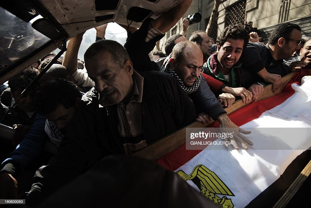 Mourners carry the coffins of killed Egyptian activists Amro Saad and Mohammed al-Guindi during their funeral outside Omar Makram Mosque in Cairo's Tahrir Square on February 4, 2013. Saad died in clashes during anti-government protests on February 1, while Guindi, 28, went missing last month after joining protests demanding change on the second anniversary of Egypt's uprising against former president Hosni Mubarak and then slipped into a coma following days in police custody, according to the health ministry and his party.