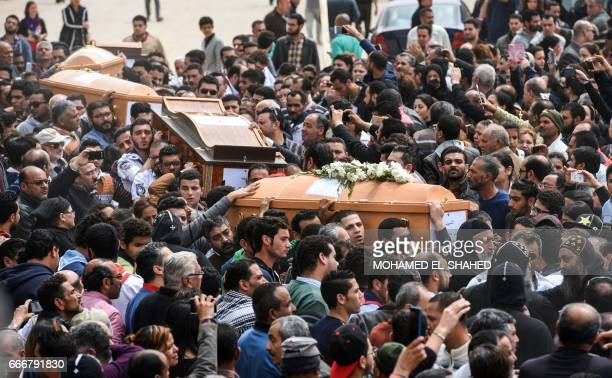 Mourners carry the coffins of the victims of the blast at the Coptic Christian Saint Mark's church in Alexandria the previous day during a funeral...