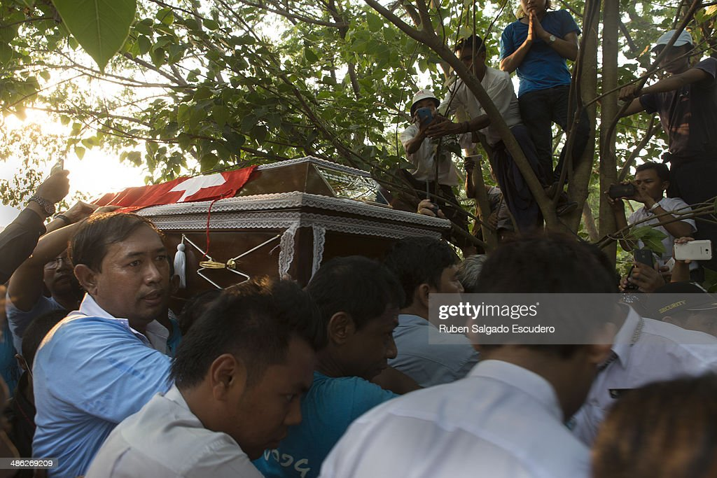 Mourners carry Win Tin's body towards the burial site during his funeral in Yay Way cemetery on April 23, 2014 in Yangon, Burma. The Burmese journalist who helped Aung San Suu Kyi launch a pro-democracy movement against the junta military regime, died April 21 in Rangoon.
