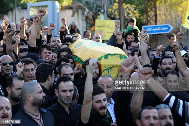 Mourners chant slogans as they carry the body of Adel Termos who was killed in a twin bombing attack that rocked a busy shopping street in the area...