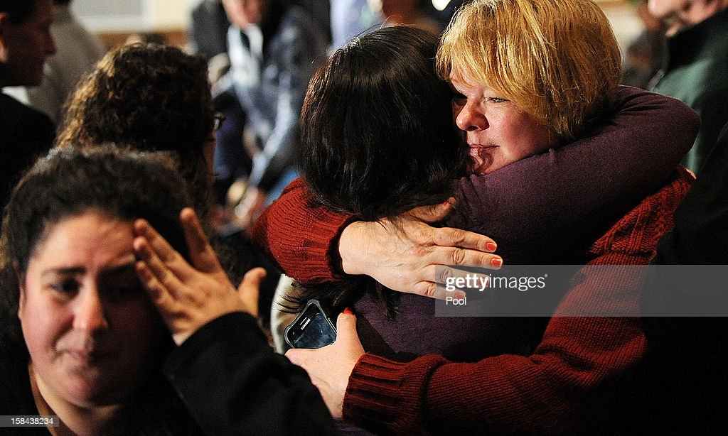 Mourners comfort one another before U.S. President Barack Obama speaks at an interfaith vigil for the shooting victims from Sandy Hook Elementary School on December 16, 2012 at Newtown High School in Newtown, Connecticut. Twenty-six people were shot dead, including twenty children, after a gunman identified as Adam Lanza opened fire at Sandy Hook Elementary School. Lanza also reportedly had committed suicide at the scene. A 28th person, believed to be Nancy Lanza, found dead in a house in town, was also believed to have been shot by Adam Lanza.