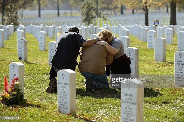 Mourners console each other on Veteran's Day at the Tomb of the Unknown Soldier in Arlington National Cemetery on November 11 2012 in Arlington...