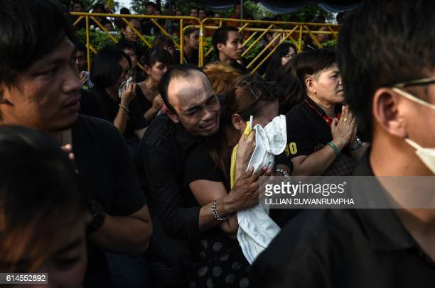 Mourners cry as the hearse carrying the body of the late Thai King Bhumibol Adulyadej passes the Grand Palace in Bangkok on October 14 2016 Massive...