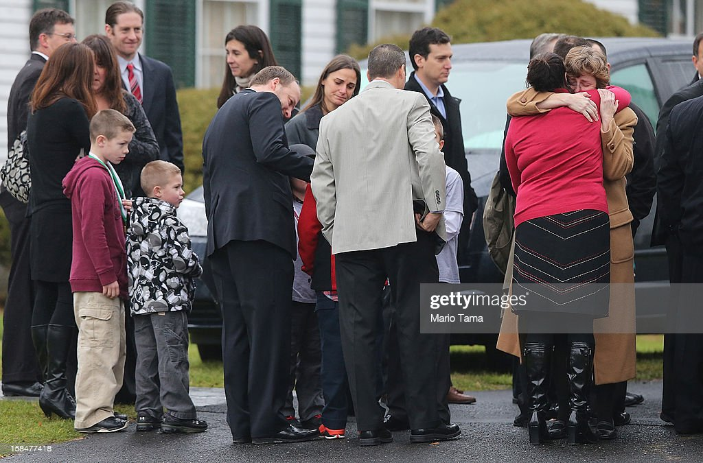 Mourners embrace as others wait to enter Honan Funeral Home before the funeral for six-year-old Jack Pinto on December 17, 2012 in Newtown Connecticut. Pinto was one of the 20 students killed in the Sandy Hook Elementary School mass shooting.