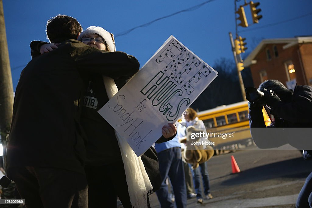 Mourners embrace at a memorial for massacre victims on December 20, 2012 in Newtown, Connecticut. Six funeral services were held Thursday for students and teachers in the Newtown area.