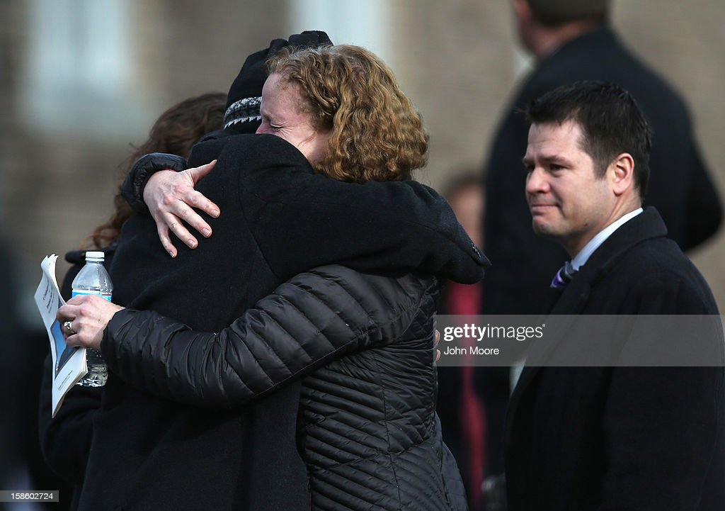 Mourners embrace following a funeral for Benjamin Wheeler, 6, at the Trinity Episcopal Church on December 20, 2012 in Newtown, Connecticut. Benjamin, a member of Tiger Scout Den 6, was killed when 20 children and six adults were massacred at Sandy Hook Elementary School last Friday. Six services were held for students and teachers in the Newtown area Thursday.