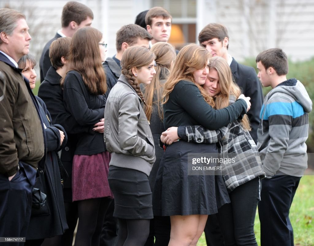 Mourners embrace following services for six year-old Noah Pozner, who was killed in the December 14, 2012 shooting massacre in Newtown, Connecticut, at Abraham L. Green and Son Funeral Home on December 17, 2012 in Fairfield, Connecticut. Today is the first day of funerals for some of the twenty children and seven adults who were killed by 20-year-old Adam Lanza on December 14, 2012. AFP PHOTO / Don EMMERT