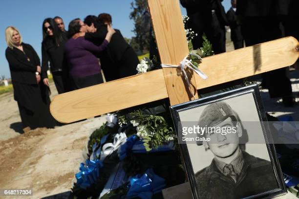 Mourners embrace near the grave of Georgiou Theodoulos Theodoulou at his funeral on March 5 2017 in Pera Chorio Nisou Cyprus Theodoulou was an...