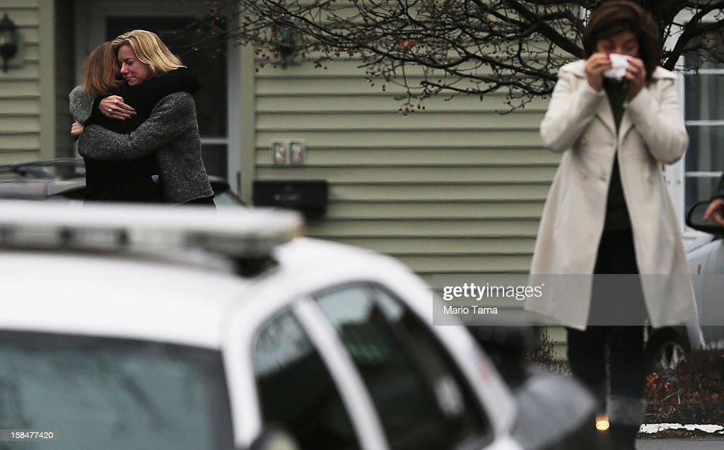 Mourners embrace while deparing Honan Funeral Home after the funeral for six-year-old Jack Pinto on December 17, 2012 in Newtown Connecticut. Pinto was one of the 20 students killed in the Sandy Hook Elementary School mass shooting.