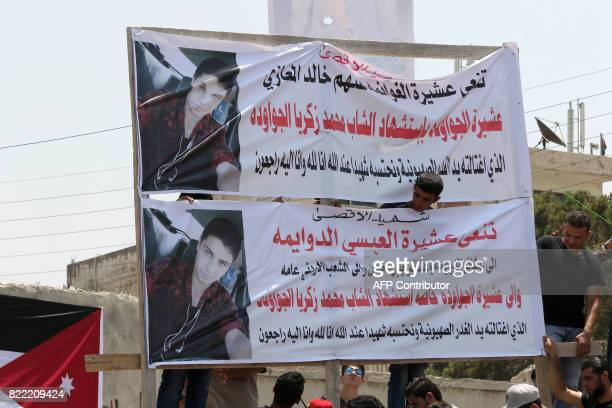 Mourners erect banners bearing the portrait of 17yearold Mohammed Jawawdeh who was killed on the weekend when he attacked a security guard at the...