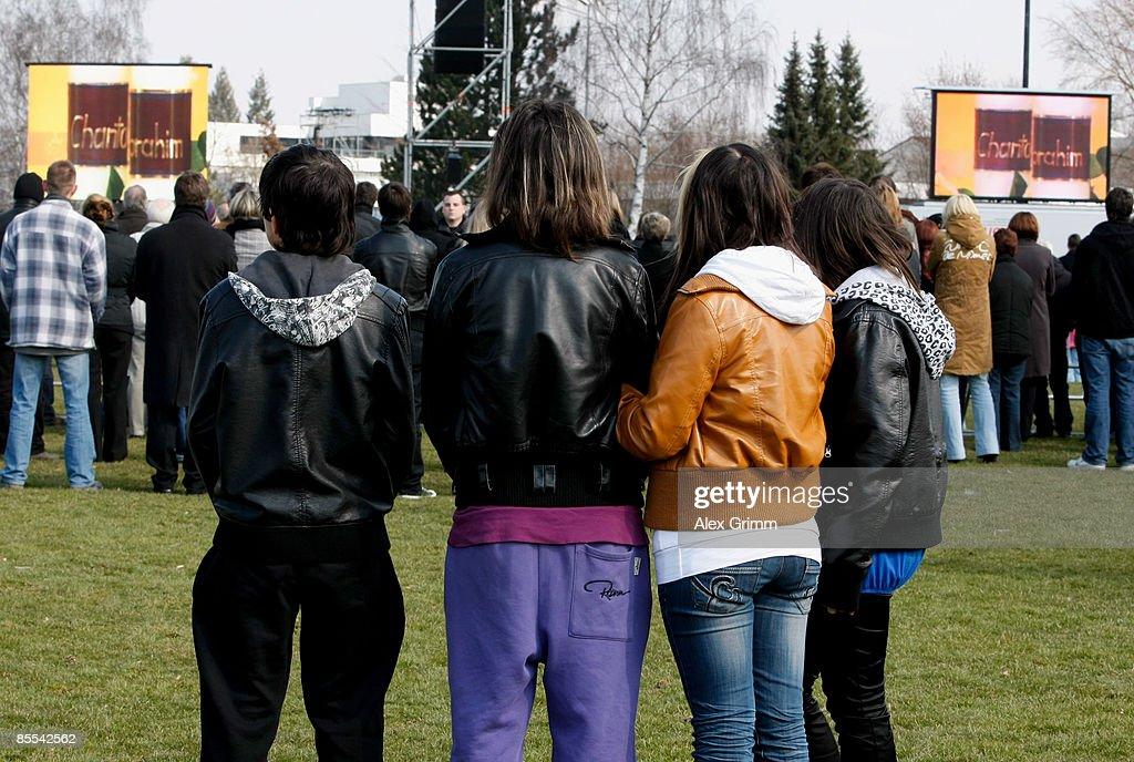 Mourners follow a church service on video screens at a sports field near Albertville high school on March 21 2009 in Winnenden near Stuttgart Germany...