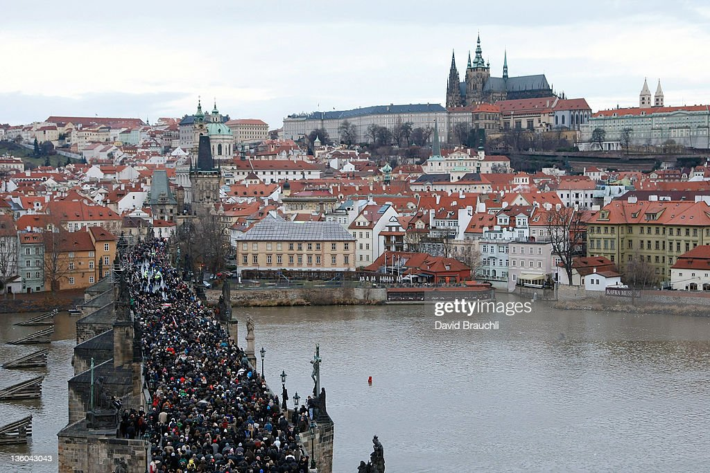 Mourners follow a hearse carrying the coffin of former Czech President Vaclav Havel across Charles Bridge on its way to Prague Castle on December 21...