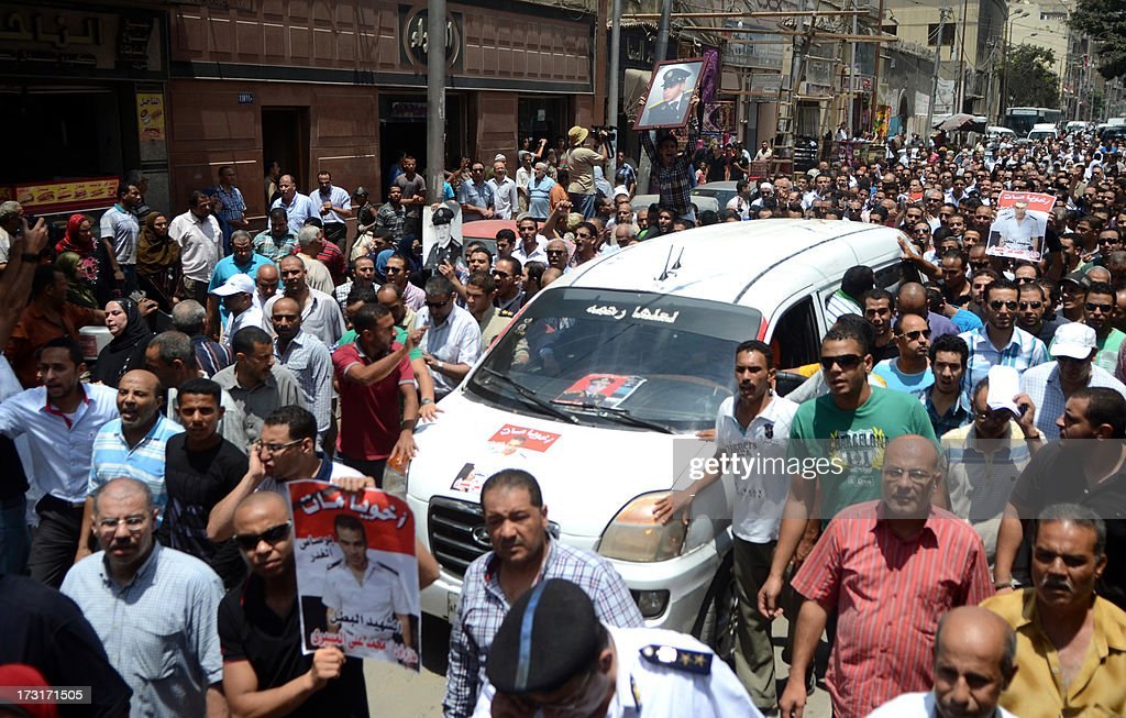 Mourners follow a vehicle carrying the coffin of a police officer killed in clashes between protestors and security forces during his funral in the northern coastal city of Alexandria on July 9, 2013. Egypt's interim leader vowed fresh elections by early next year as Islamists prepared to rally after dozens of ousted president Mohamed Morsi's loyalists died in clashes at a Cairo military barracks the day before. The Muslim Brotherhood released the names of 42 people killed in the incident, as the interior ministry and military said two policemen and a soldier were also killed. AFP PHOTO/ STR