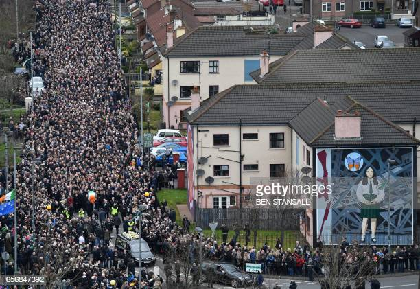 TOPSHOT Mourners form a funeral procession as they make their way with the coffin past a Republican mural to St Columba's Church Long Tower for the...