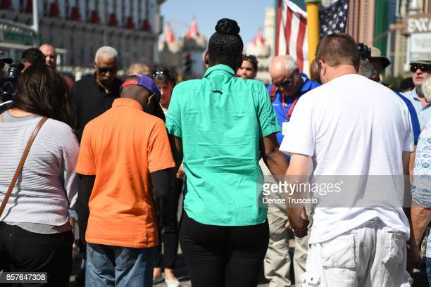 Mourners form a prayer circle at a memorial on Las Vegas Boulevard and Reno Avenue for the victims of the Route 91 Harvest country music festival...