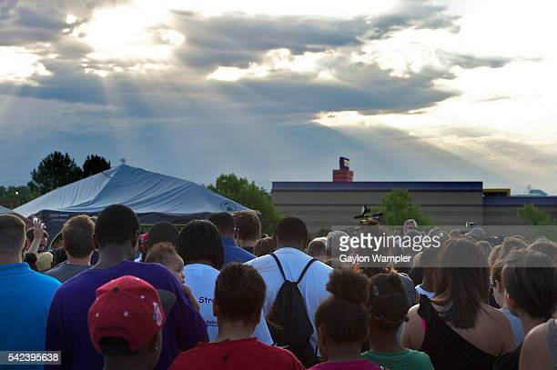 Mourners gather across the street from the Century 16 movie theater Friday night to mourn together the loss of 12 lives and the injury of dozens more...