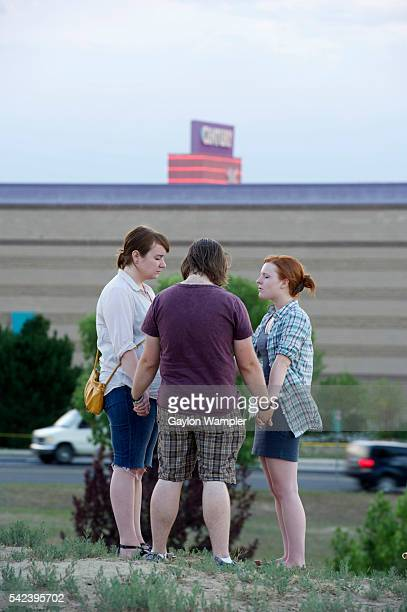 Mourners gather across the street from the Century 16 movie theater Friday night to mourn and pray together the loss of 12 lives and the injury of...