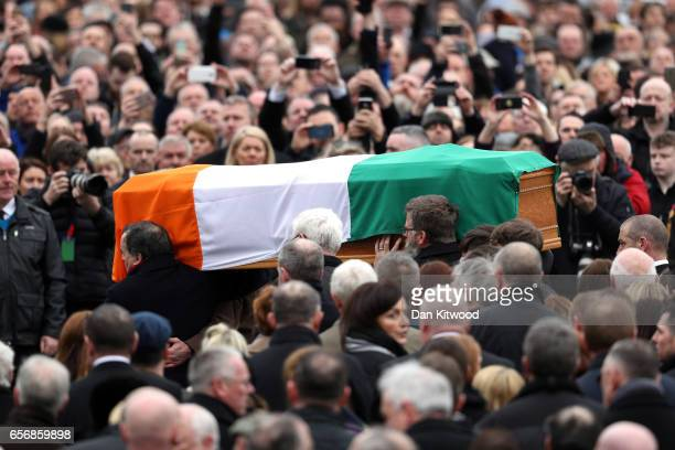 Mourners gather as the coffin of the late Martin McGuinness is carried through the streets of Derry on March 23 2017 in Londonderry Northern Ireland...