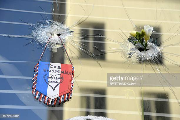Mourners gather at a makeshift memorial on November 15 2015 outside of La Belle Equipe bar on rue de Charonne following a series of coordinated...