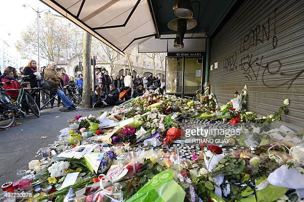Mourners gather at a memorial site with flowers candles and signs on November 15 outside of the Le Belle Equipe in the 11th district of Paris for...