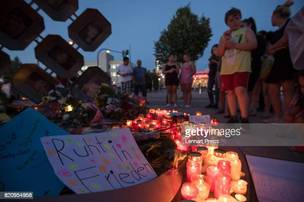 Mourners gather at a memorial to commemorate the victims of the shooting spree that one year ago left ten people dead including the shooter on July...