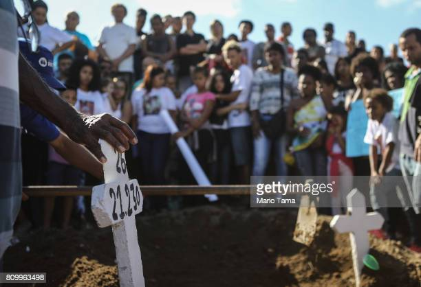 Mourners gather at the burial of Vanessa dos Santos who was shot in the head and killed in the doorway of her house during a shootout involving...