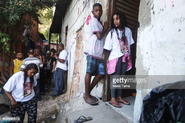 Mourners gather at the doorway where Vanessa dos Santos was shot in the head and killed during a shootout involving police and gang members in the...