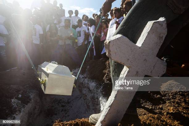 Mourners gather during the burial of Vanessa dos Santos who was shot in the head and killed in the doorway of her house during a shootout involving...