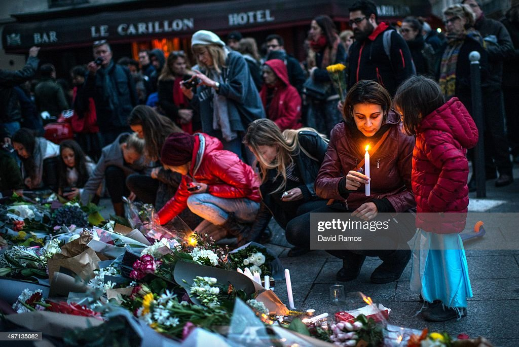 Mourners gather in front of the Petit Cambodge and Le Carillon restaurants on November 14 2015 in Paris France At least 120 people have been killed...