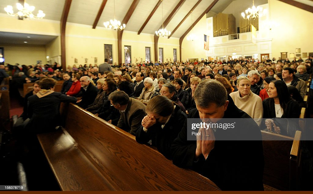 Mourners gather inside the St. Rose of Lima Roman Catholic Church at a vigil service for victims of the Sandy Hook School shooting December 14, 2012 in Newtown, Connecticut. Twenty-seven people are dead, including 20 children, after a gunman identified as Adam Lanza in news reports opened fire in the school. Lanza also reportedly died at the scene.