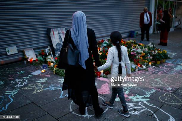 Mourners gather to pay their respects outside the Edeka supermarket where on Friday Ahmad A killed one and injured six people with a knife on July 28...