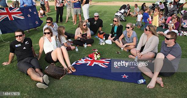 Mourners gather with the New Zealand flag at a make shift memorial at the 'Aspire Zone' close to the scene where twoyearold New Zealand triplets...