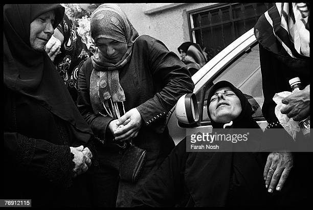 Mourners grieve during a mass funeral service in Qana southern Lebanon August 18 2006 Many of those buried Friday were killed in an Israeli airstrike...