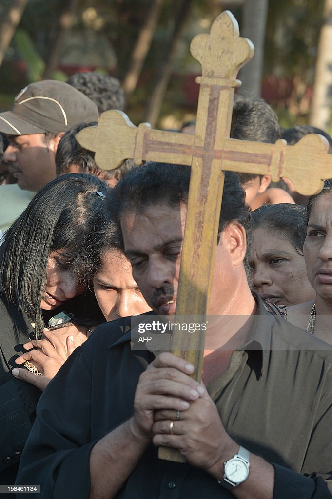 Mourners grieve during the funeral of nurse Jacintha Saldanha at The Shirve Church cemetary near Mangalore on December 17, 2012. About 2,000 mourners have packed a Catholic church in southwest India for the funeral of the nurse who was found hanged after taking a hoax call to the hospital treating Prince William's wife. Indian-born Jacintha Saldanha, 46, apparently committed suicide after answering the telephone call from Australian radio DJs to the hospital where the pregnant Duchess of Cambridge was admitted with acute morning sickness. AFP PHOTO/Manjunath KIRAN