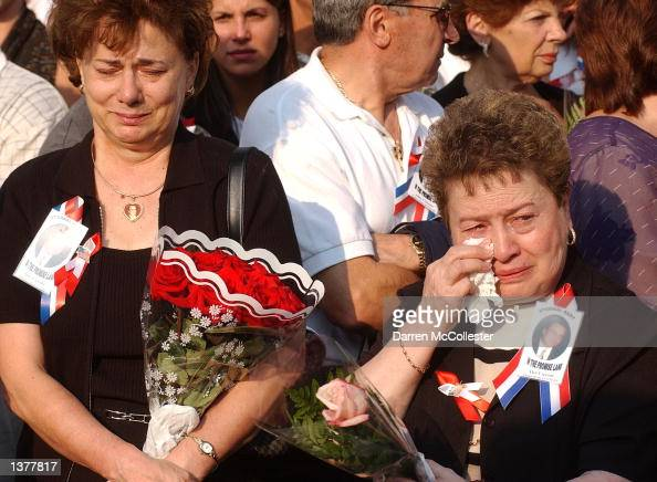 Mourners grieve during the World Trade Center memorial service at Ground Zero the morning of September 11 2002 in New York City Memorial services...