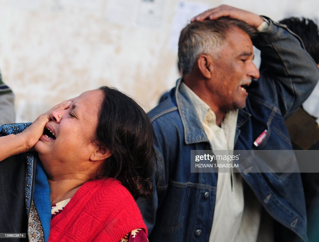 Mourners grieve following the attack on a lawmaker and his guards in Karachi on January 17, 2013. A Pakistani lawmaker from a coalition partner in the government was shot dead with three of his guards in a drive-by shooting in Karachi on Thursday, police said. AFP PHOTO/Rizwan TABASSUM