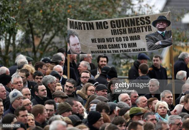 Mourners hold a banner as they gather outside St Columba's Church on March 23 2017 in Londonderry Northern Ireland The funeral is held for Northern...