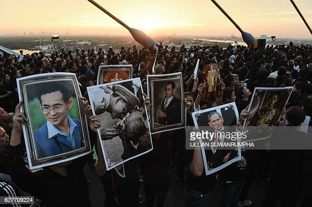 Mourners hold aloft pictures of the late Thai King Bhumibol Adulyadej as people gather to commemorate his birthday on top of Bhumibol Bridge in...