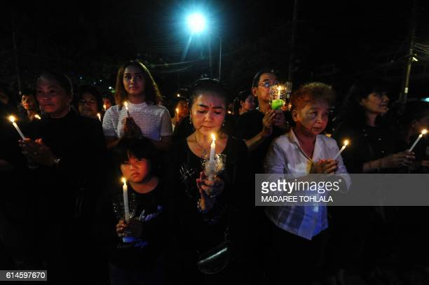 Mourners hold candles to pay respects to the late Thai King Bhumibol Adulyadej in the southern province of Narathiwat on October 14 2016 Massive...