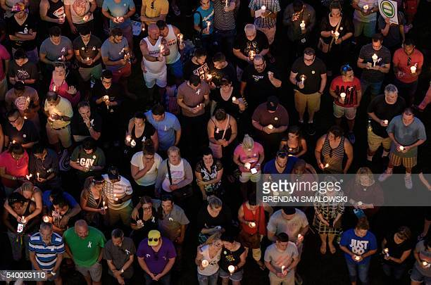 Mourners hold candles while observing a moment of silence during a vigil outside the Dr Phillips Center for the Performing Arts for the mass shooting...
