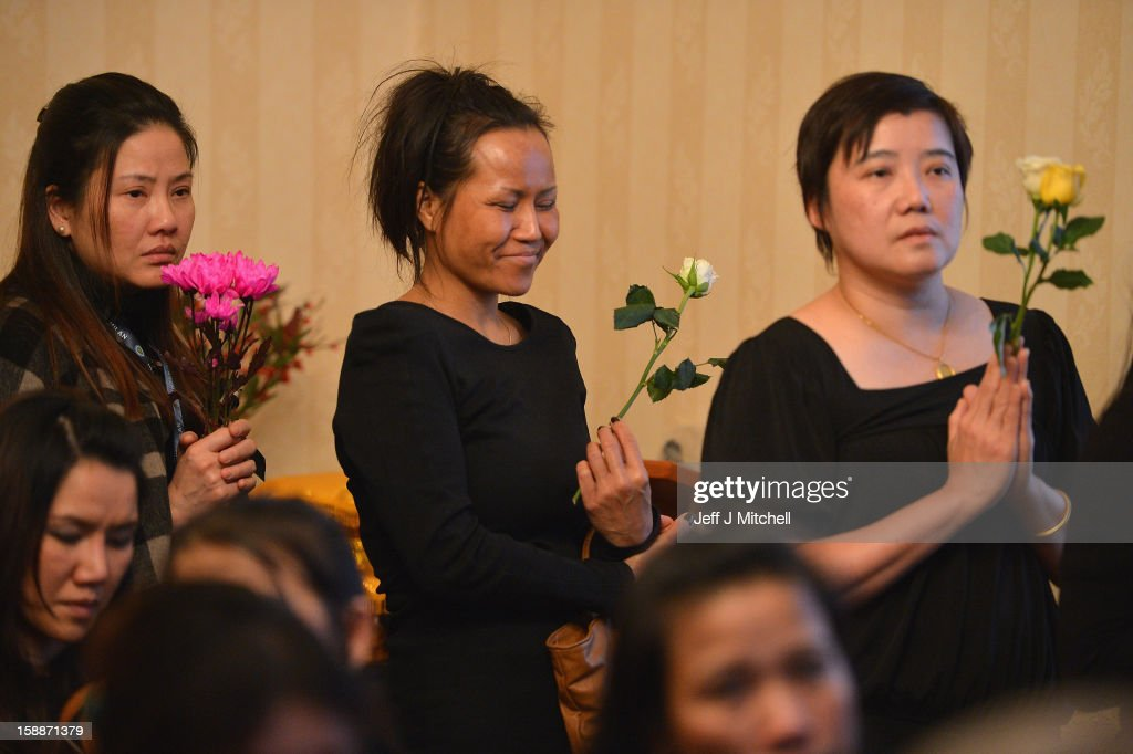 Mourners hold flowers as they grieve at a service of remembrance for three Thai Buddhist Monks who died in a car crash on Christmas Eve, at Oakvale Funeral Home on January 2, 2013 in Edinburgh, Scotland. Abbot Phramaha Pranom Thongphaiboon, 43, head of the Thai Buddhist community in Aberdeen, was killed in a car crash on Christmas Eve along with his colleagues Phramaha Kriangkrai Khamsamrong, 35, and Phramaha Chai Boonma, 36. The three men were travelling to the Dhammapadipa Temple in Edinburgh when they were involved in the head-on collision on the A68 near Pathhead, Midlothian.