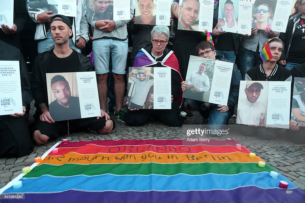 Mourners hold photographs of victims of a shooting at a gay nightclub in Orlando, Florida nearly a week earlier, during a vigil in front of the United States embassy for them on June 18, 2016 in Berlin, Germany. Fifty people were killed and at least as many injured during a Latin music event at the Pulse club in the worst terror attack in the U.S. since 9/11. The American-born gunman had pledged allegiance to ISIS, though officials have yet to find conclusive evidence of his having any direct connection with foreign extremists. The incident has added fuel to the ongoing debate about gun control in the country.
