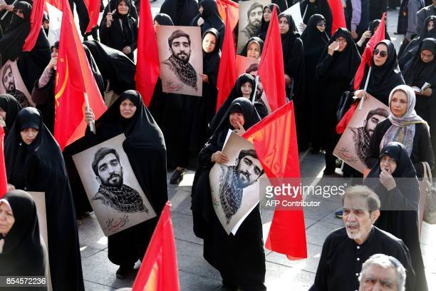 Mourners hold portraits of Mohsen Hojaji a young member of Iran's elite revolutionary guards Corps who was beheaded in Syria by Islamic State group...